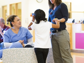 Dr. Jean Mulcahy-Levy helps a kid stand up while a woman in scrubs watches.
