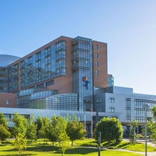 The view of Children's Hospital Colorado from across the street. The sky is blue. The building is a light brown with blue glass windows. The land in front of the hospital is green grass with lots of green, yellow and red trees.