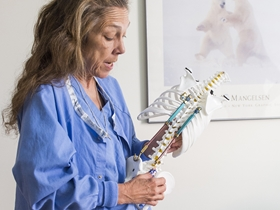Dr. Hadley Miller holds a spine model to demonstrate scoliosis research.