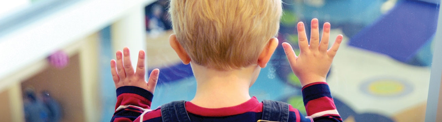 A young blond hair boy wearing a blue and red striped shirt and overalls presses his hands against a window overlooking the Children's Hospital Colorado atrium.