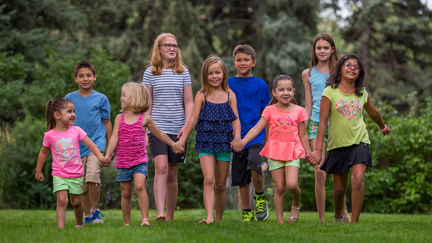 A group of 9 kids - five in front and four in back - hold hands and walk in a grassy field with trees behind them. The kids are ages 4-15 and wearing brightly colored clothes in a variety of colors.