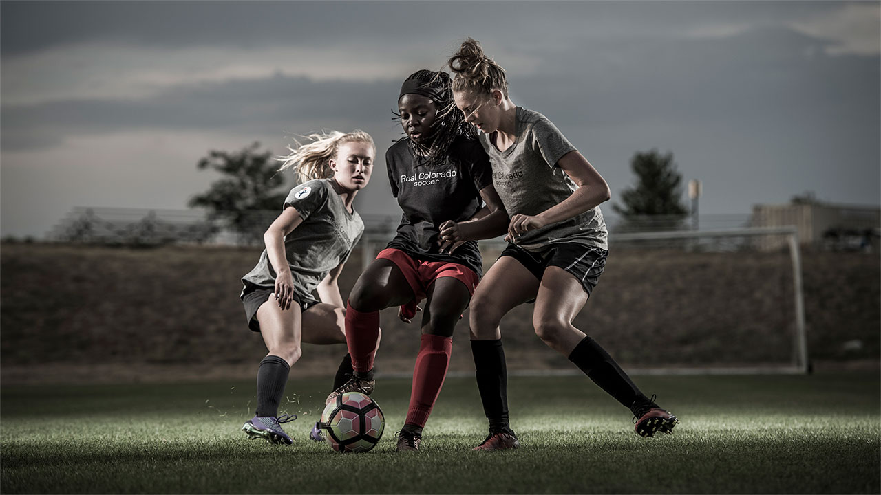 Two teenage girls try to take the ball away from a third teenage girl on a soccer field.