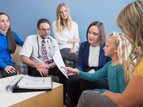(From left) Pediatric gastroenterologist Edward Hoffenberg, MD; genetic counselor Alexandra Suttman, MS, CGC; and pediatric oncologist Lindsey Hoffman, DO, talk genetics with a patient and her mom.