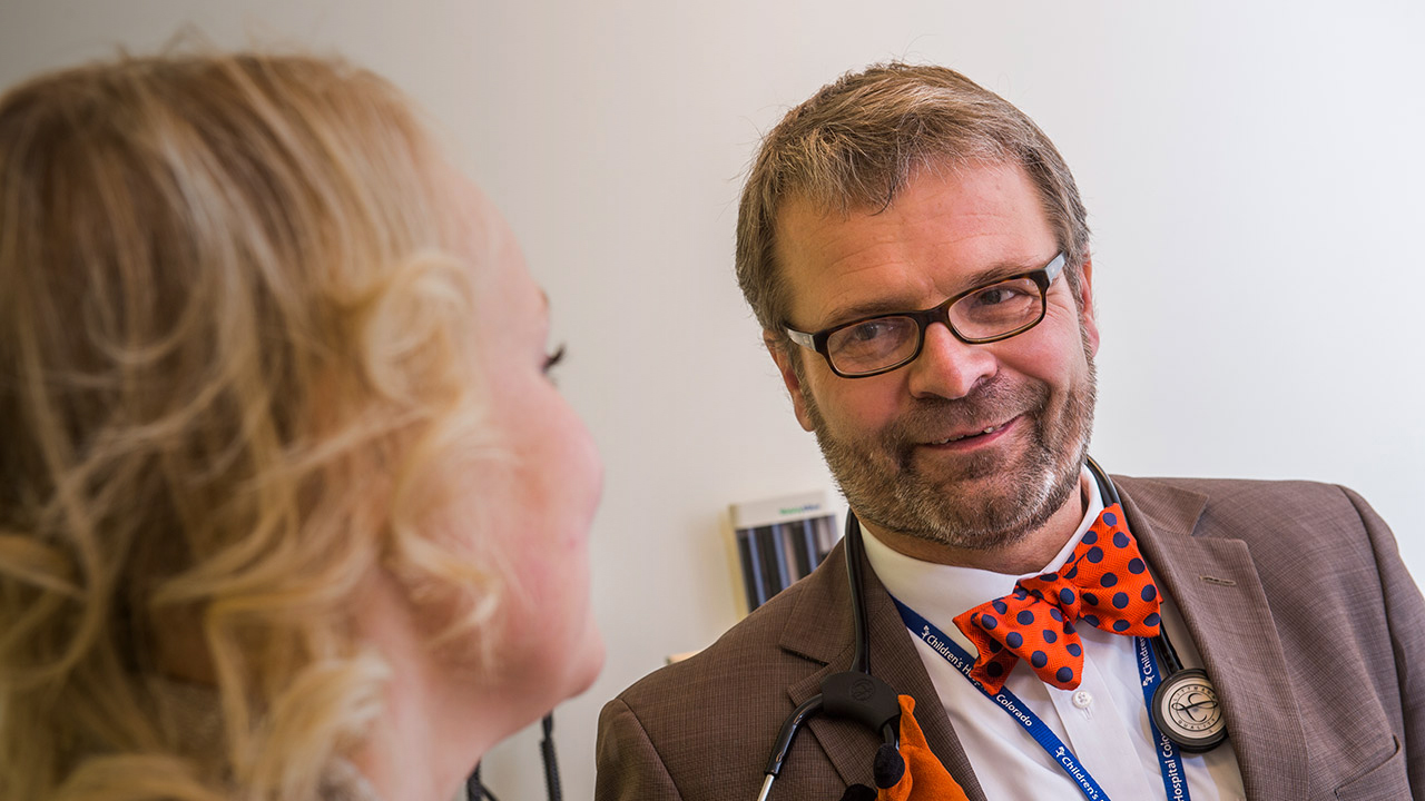 A man with glasses is wearing a polkadot bow-tie and brown suite. He has a stethoscope around his neck and is talking to a blonde woman who is facing him.