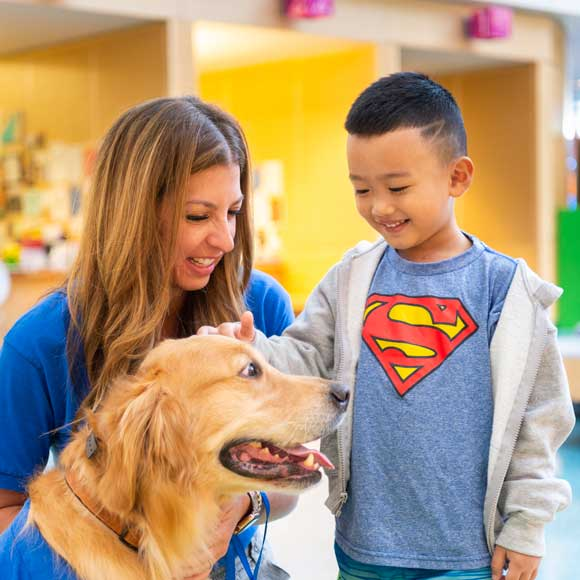 Photo of a young boy smiling as he visits with a volunteer and her golden retriever in the Prescription Pet Program.