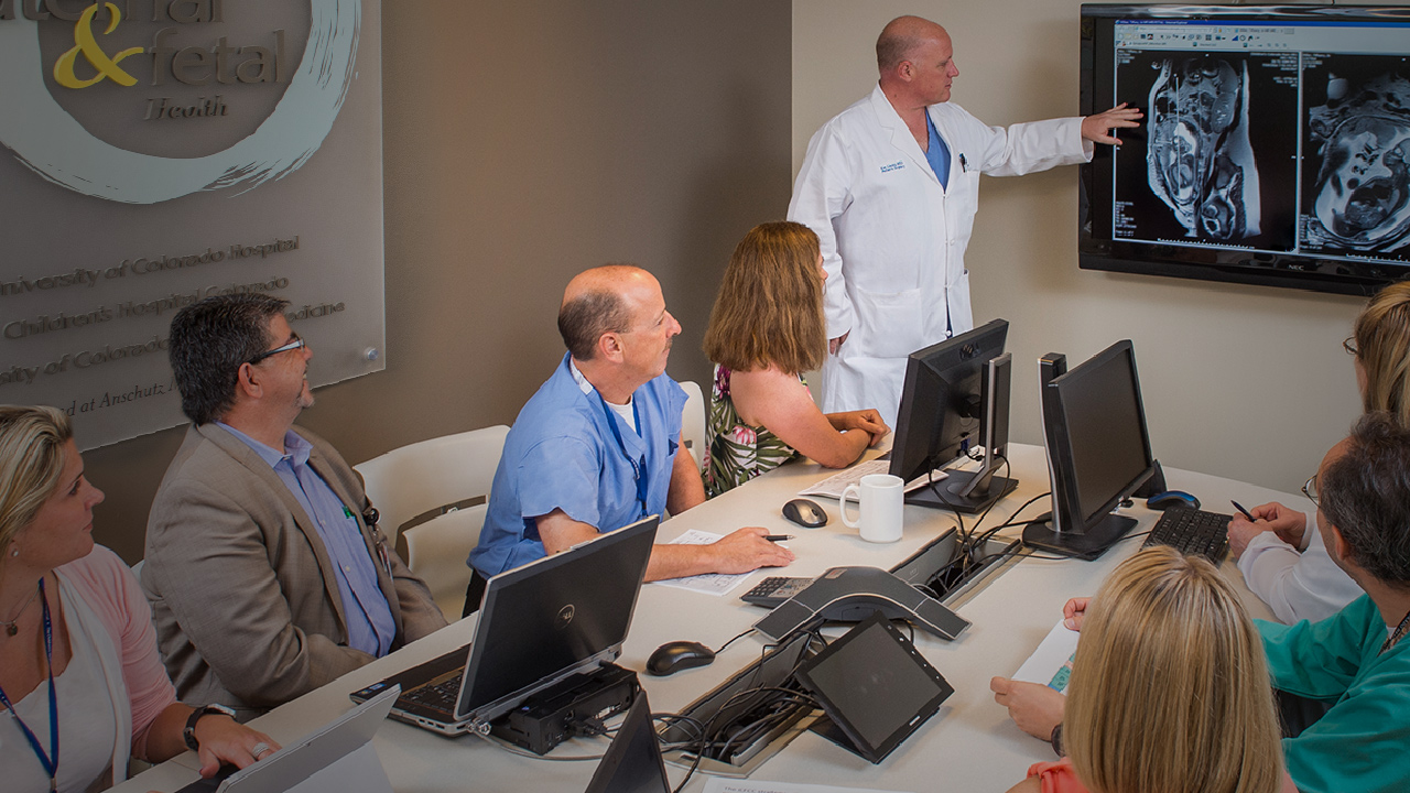 A group of doctors sit around a table with laptops while another doctor in a white coat stands next to a screen pointing to medical images.