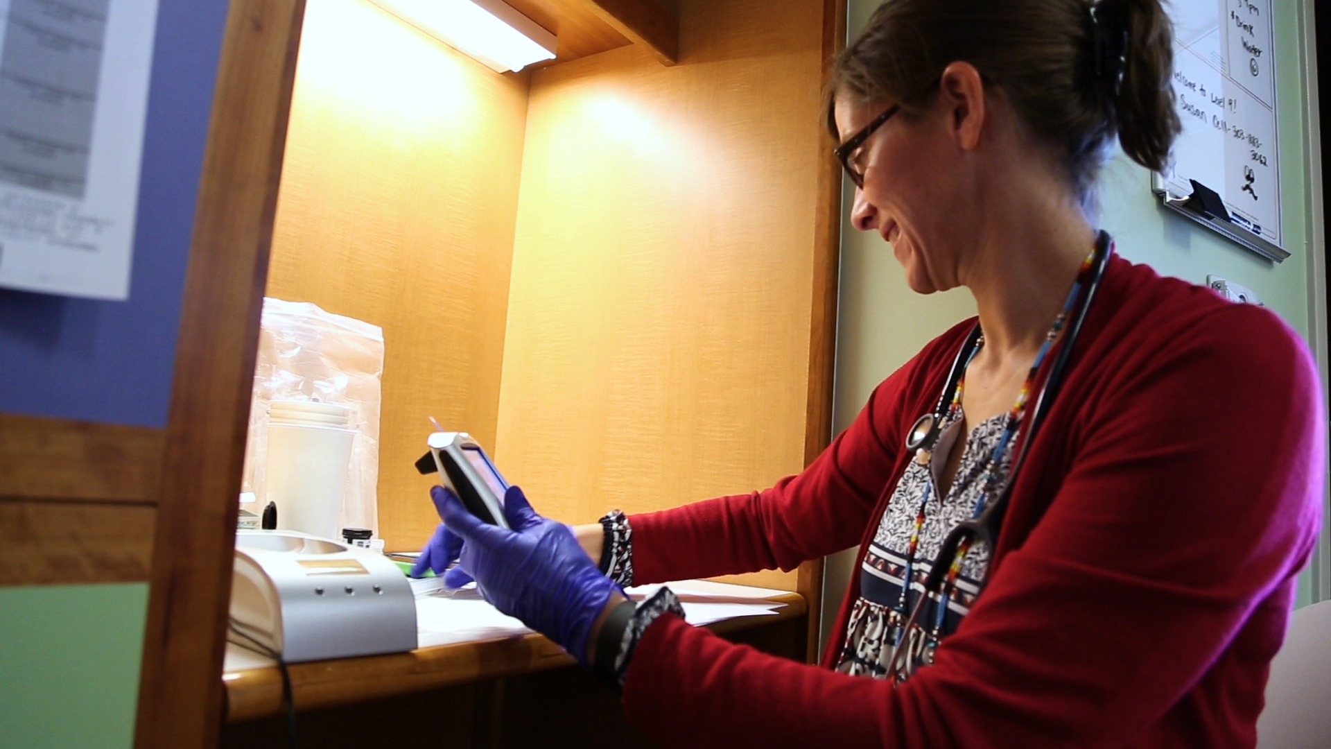 Doctor Kristen Nadeau, Children's Hospital Colorado, wears blue gloves while handling a medical device.