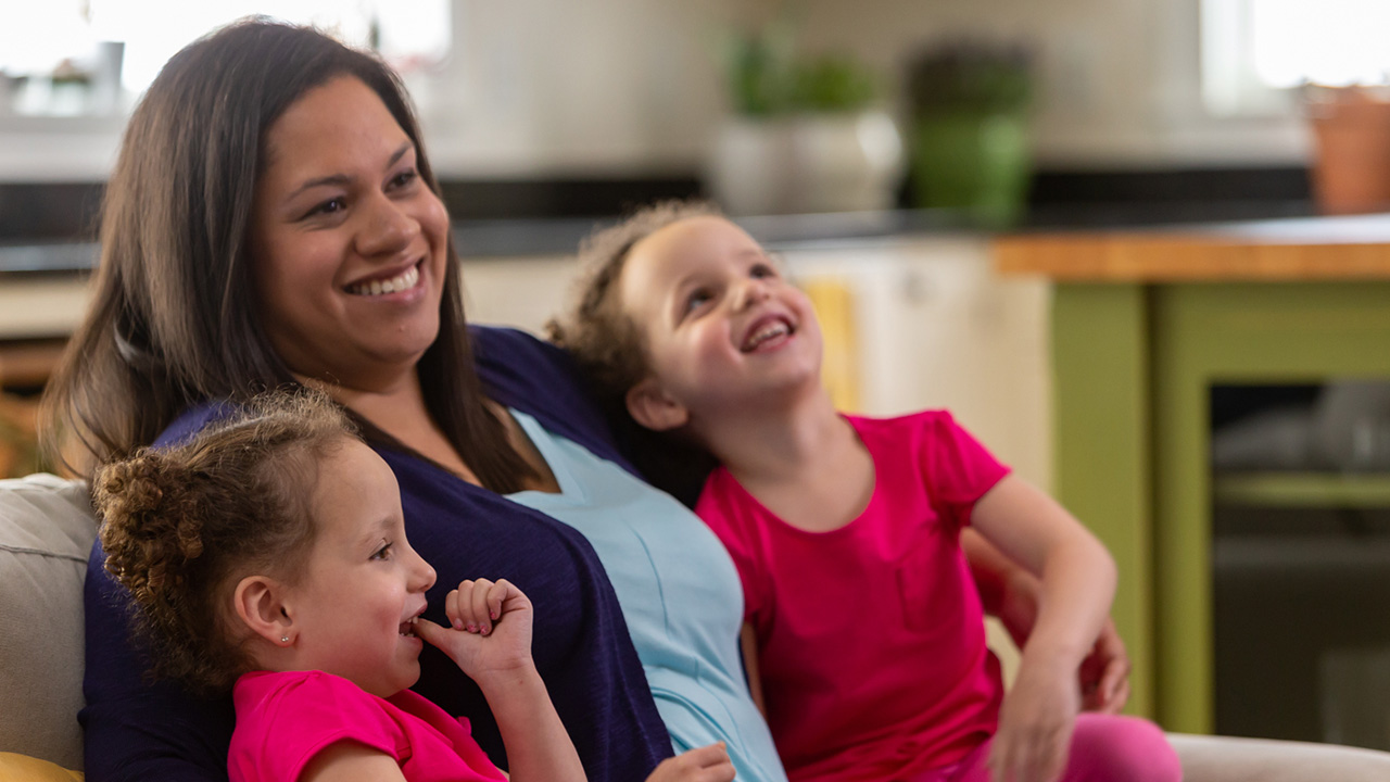 Nicole, treated for TTTS at Children's Colorado, sits with her school-age twin girls.