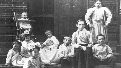 Old photo of child patients from 1910 including a baby in a wood high chair and a school age girl on crutches