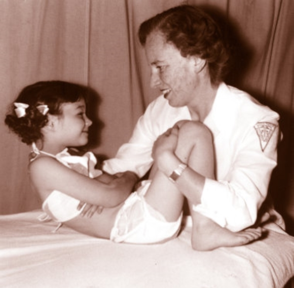 An old photo of a woman in white holds a young girl while bending her legs