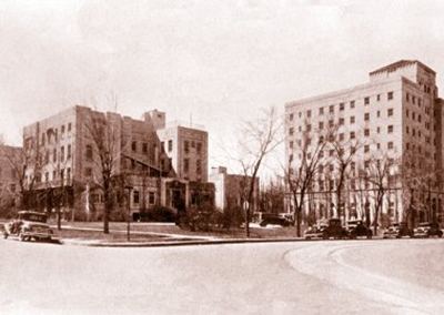 An old photo of the exterior of The Children's Hospital in 1932, showing two brick buildings with lots of windows.