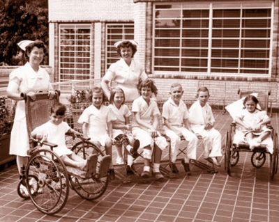 An old photo of five children sitting on a bench outside of The Children's Hospital while two children sit in wheelchairs on either side of them; two nurses in white dresses and white hats stand behind them.