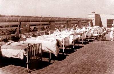 An old photo of 9 hospital beds lined up on the roof so the patients in them can get some sun