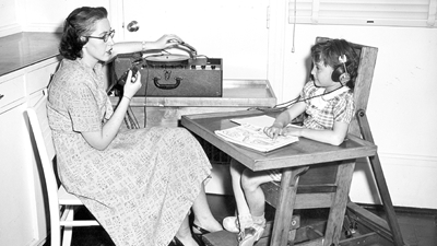 A black and white photo of a woman in a long dress with shoulder length brown hair and glasses speaking into a microphone and adjusting the speaker case while a young patient listens on headphones and sits in a chair with attached desk.