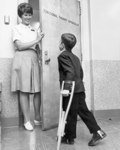A black and white photo of a women in a white shirt and light color skirt standing in an ajar door greeting a school age boy in dark suit using crutches. The door says Functional Therapy Gymnasium on it.