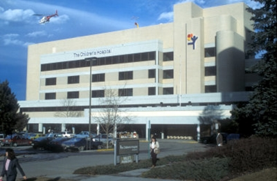 Outside view of The Children's Hospital with three rows of windows and the balloon boy logo on the building while a helicopter flies away in the bright blue sky.