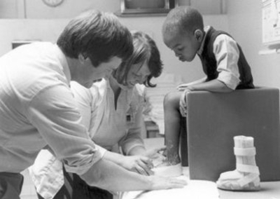 A black and white photo of Dr. Dennis Matthews with dark hair and a mustache standing next to a woman while they look at a young boy's foot. The boy is sitting on a small chair on the table and there is a foot brace sitting next to the chair.