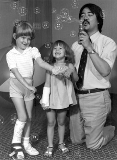 Black and white photo of Dr. Frank Chang with dark hair and a mustache, wearing a short sleeve shirt and tie, kneeling on the ground and blowing bubbles for two young girls trying to catch them. One girl has a cast on her foot and the other has a cast on her arm.