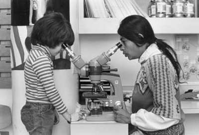 Black and white photo of a woman (Dr. Taru Hays) with long dark hair looking into a microscope with two viewfinders. A young kid wearing a striped shirt looks into the other viewfinder on the other side of the microscope.
