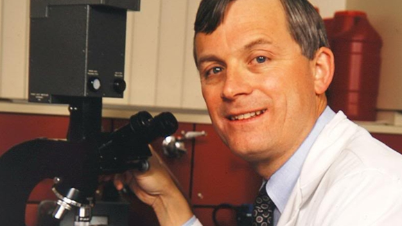Dr. James Todd, wearing a white lab coat and tie, holds onto a microscope while he looks up and smiles
