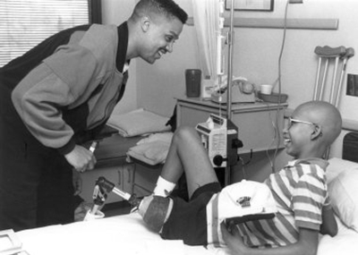 A black and white photo of Denver Nuggets basketball player Chris Jackson leaning over a patient and smiling while the boy looks up from the bed and smiles. The boy is holding a Denver Nuggets hat, wearing a striped shirt, has glasses and a prosthetic for his left leg.