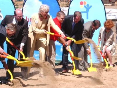 Four men in suits, two women in nice clothes, and a teenage boy in a red polo and khaki pants hold yellow shovels while they dig into the ground in front of Children's Hospital signs