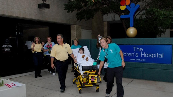 A boy in a stretcher is wheeled past a crowd of people cheering as he exits the old Children's Hospital building