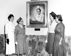 Black and white photo of four women gathered around a photo of a woman on a wall.