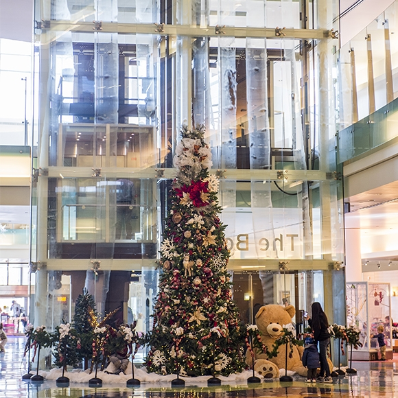A large Christmas tree in the lobby is surrounded by gifts and a giant teddy bear.