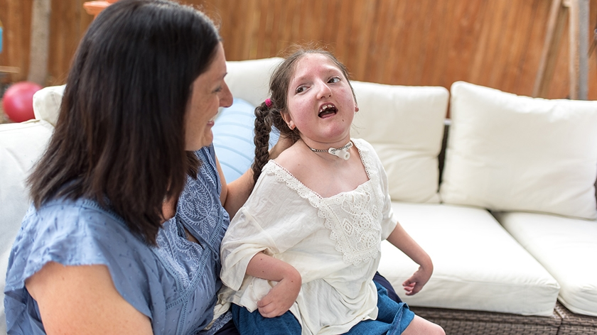 Medicaid patient Cici and her mother sit together in their backyard.