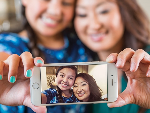 A mom and daughter take a selfie, which is displayed on an iPhone screen in the foreground