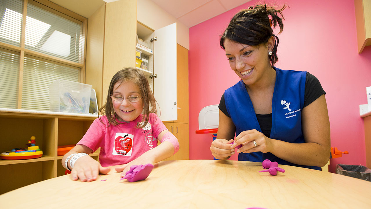 A volunteer donates her time to play with play-doh with a girl patient.