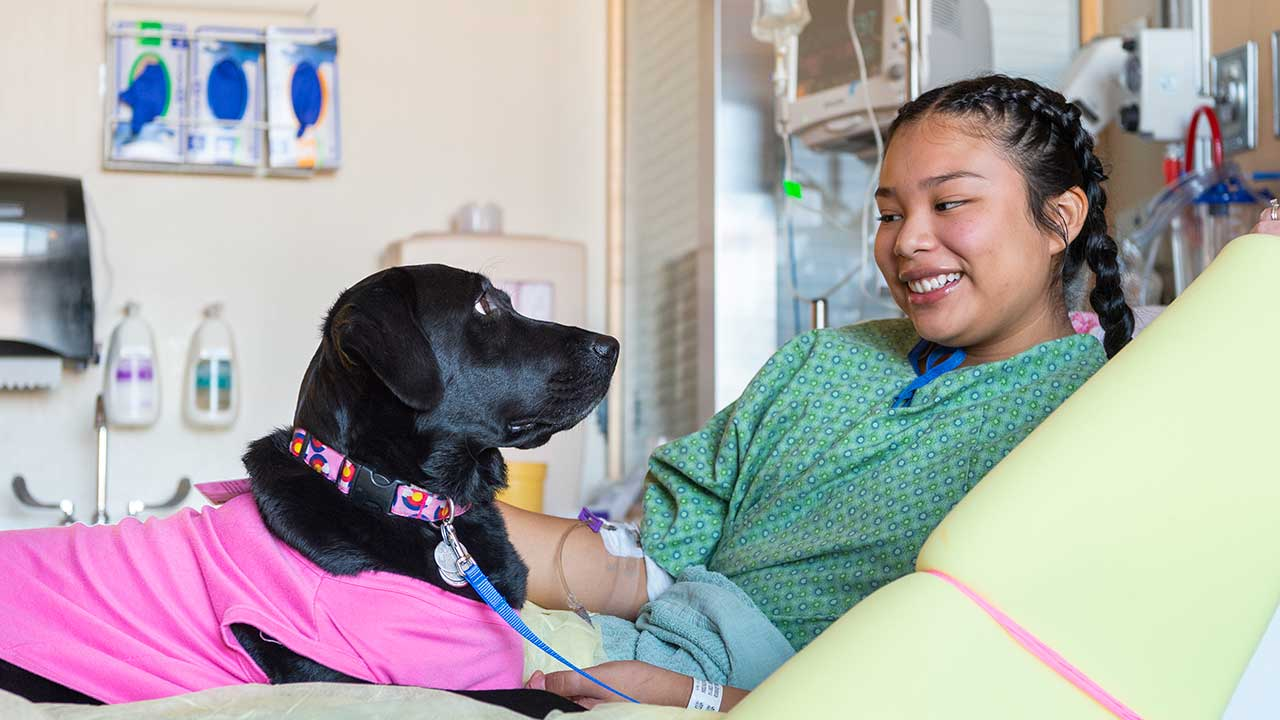 A volunteer prescription pet visits a teenage patient at Children's Hospital Colorado.