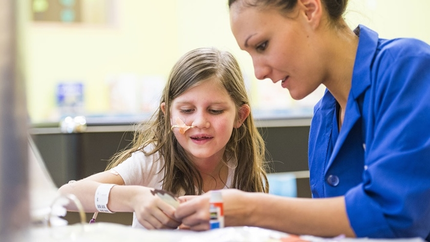 A volunteer helps a girl glue something on a piece of paper.