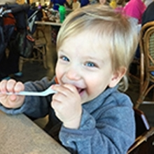 Blonde boy in a restaurant with a spoon in his mouth smiling.