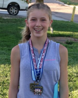 Jessie stands tall with her champion medals hanging around her neck.