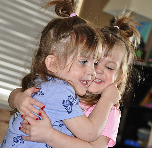 Kendall and Danika hug each other happily after surviving twin-to-twin transfusion syndrome.