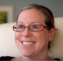 A spina bifida patient's mom smiles while telling his story.