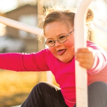 Maddie, a patient of the Sie Center, plays on a playground.