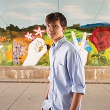 A boy with brown hair and wearing a light blue button down shirt stands in front of a colorful mural with hands spelling out L-O-V-E in sign language, a light blue sky, green grasses and several flowers including a red rose and purple lilacs.