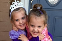 Twins Kendall and Danika, 4 years old, wearing purple and hugging each other.