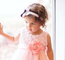 A toddler girl with brown hair stands against a window in a pink dress with a flower belt.