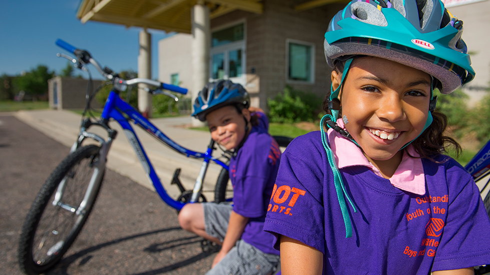Two kids in purple shirts and blue bike helmets squat down next to their blue bikes outside of a brick building.