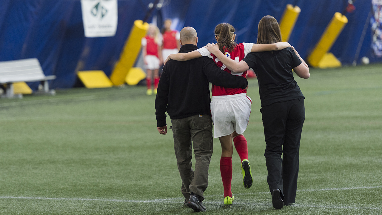 Sports doctor and athletic trainer walk young athlete off soccer field.