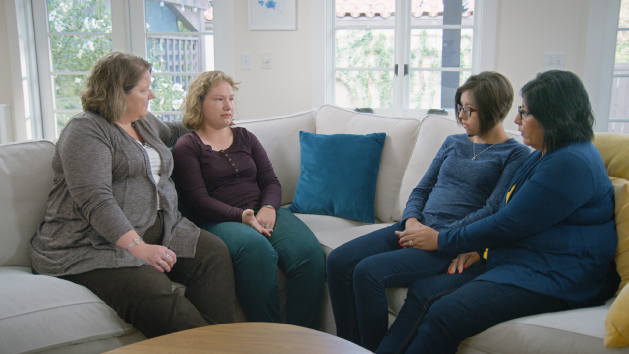 Maddie and her mom sit on a couch with Lianna and her mom, sharing how epilepsy surgery has changed their lives.