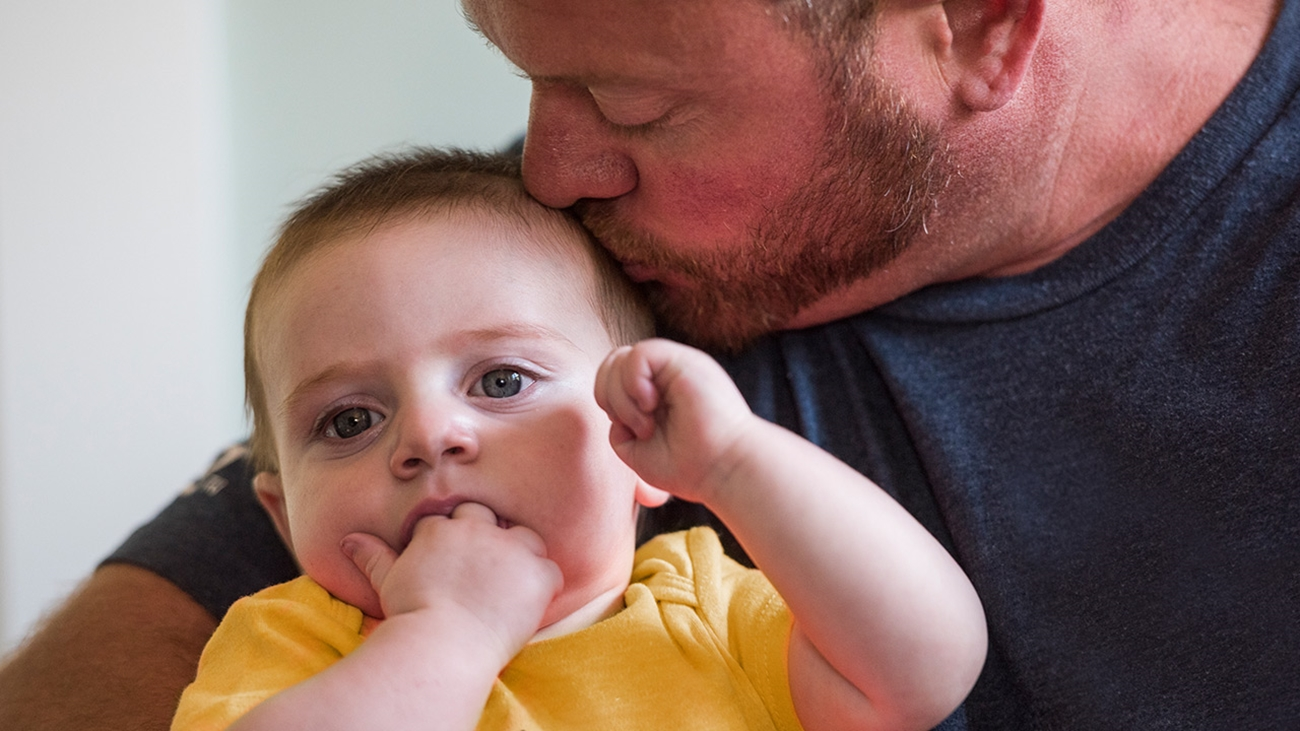 Dad Kelly kisses his son on the head. His son is being treated for HLHS at Children's Hospital Colorado.