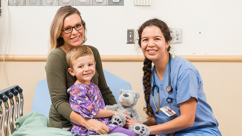 Picture of a patient and mother sitting on a hospital bed speaking with an anesthesiologist