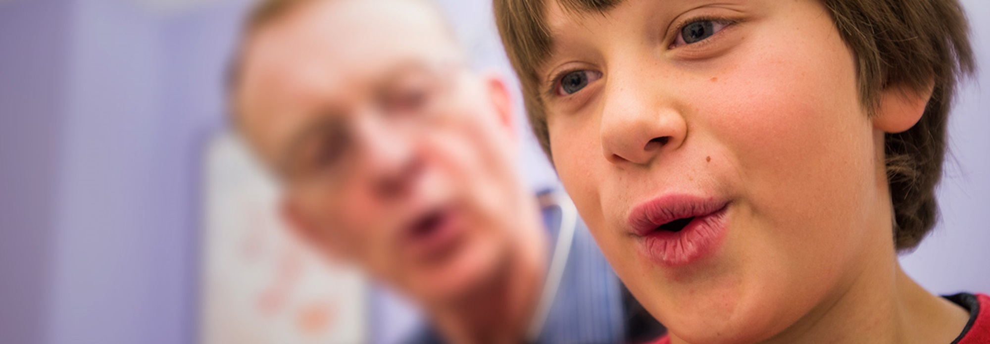 A boy with brown hair breathes out while his doctor watches in the background.