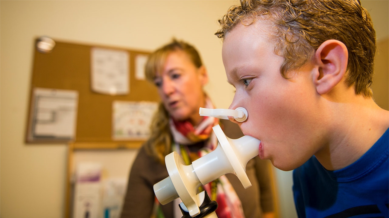 patient breathes into Pulmonary Function Laboratory device.