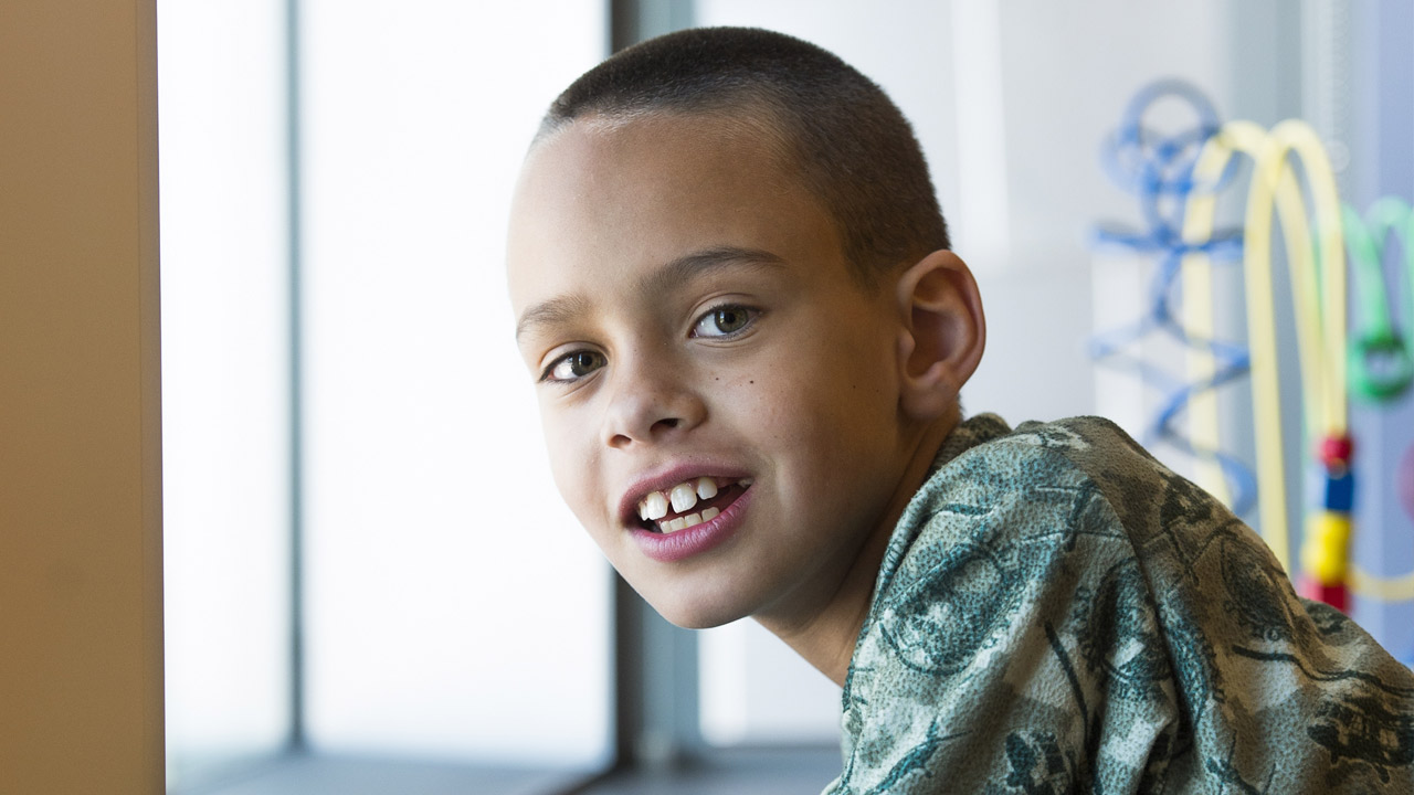Picture of a kid with buzzed brown hair and wearing a green shirt, leaning toward a window sill and smiling at the camera.
